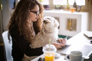 Designer working at home office and holding her puppy